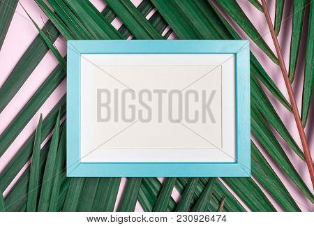 Top View Blank Blue Pastel Photo Frame On Green Palm Leaf On Pastel Pink Table Top Background.summer