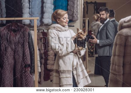 Man With Wallet And Girl With Happy Faces Hold Dog Among Furry Coats On Clothes Rack Background. Fin