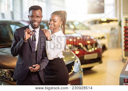 Visiting Car Dealership. Beautiful African Couple Is Holding A Key Of Their New Car, Looking At Came