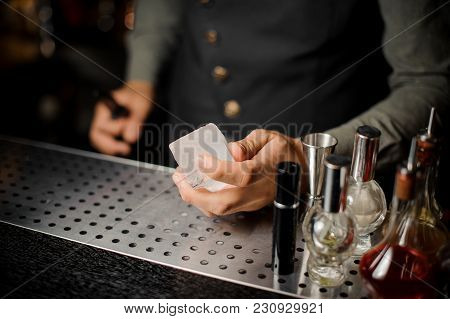 Barman Hand Holding A Large Rectangular Piece Of Ice Under The Bar Counter Among Bar Equipment