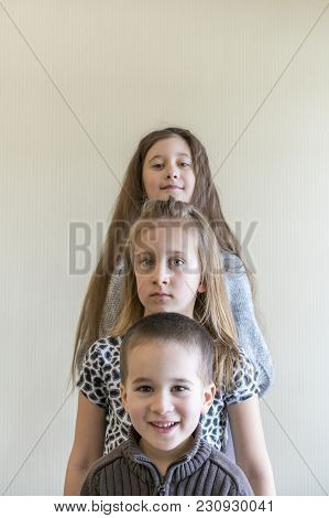 Three Children Stand In A Row. Two Girls And A Boy. Brother And Two Sisters.
