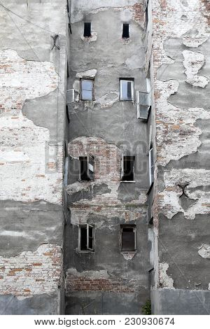Old Gray Peeling Wall With Windows In The Area Of New Praga In Warsaw. Copy Space.