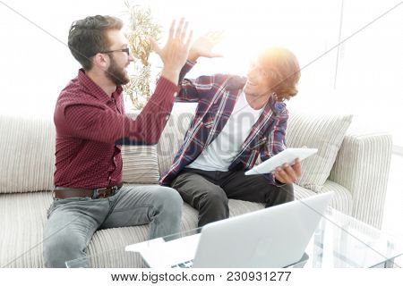 wo guys sitting on the couch and giving each other five