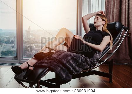 Portrait Of Female Model Wearing Short Black Dress And High Heels Relaxing On Chair.