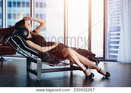 Fashion Model With Slim Long Legs Wearing Black Cocktail Dress Lying On Lounge Chair In Penthouse Ap