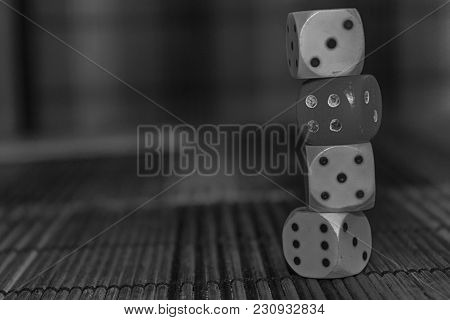 Monochrome Stack Of Three White Plastic Dices And One Red Dice On Brown Wooden Board Background. Six