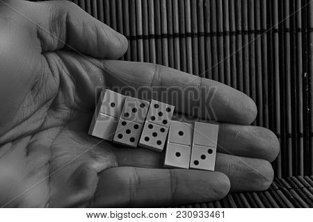 3360477 3360477 Monochrome Domino Pieces In Man's Hand, On Wooden Bamboo Brown Table Background
