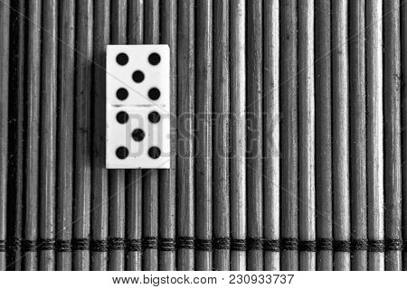 Monochrome Domino Piece On The Bamboo Brown Wooden Table Background. Domino Set - Five - 5 Dots.