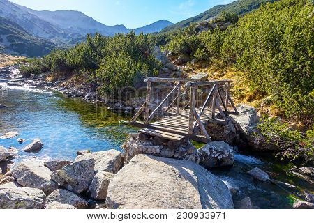Wooden Bridge Over A Small Mountain River In The Autumn Day.