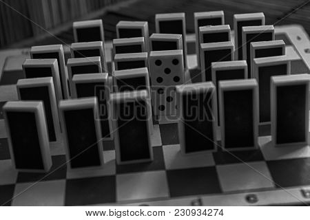Domino Pieces In A Row And One Different Statnd, Back Side, On The Bamboo Brown Wooden Table Backgro