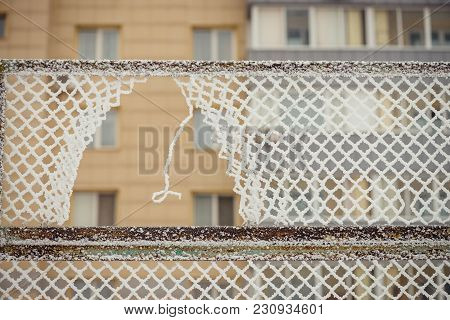 A Hole In The Fence. Rabitsa In The Hoarfrost. A Multi-storey Building On A Background.