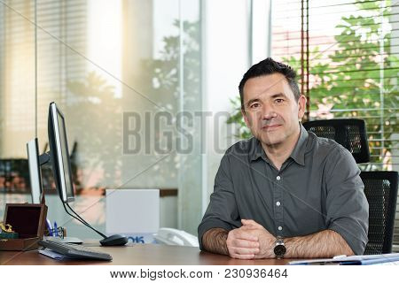 Portrait Of Smiling Entrepreneur Sitting At His Table And Looking At Camera