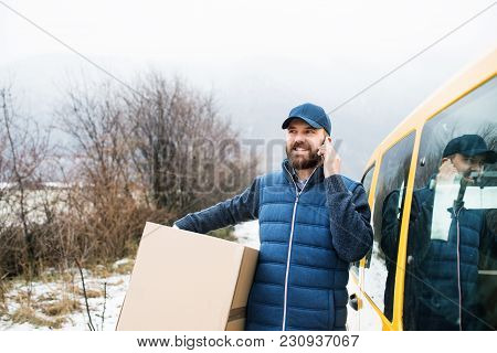Delivery Man Delivering Parcel Box To Recipient - Courier Service Concept. A Man With A Smartphone M