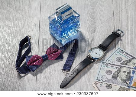 Man Perfume, Watch With A Black Leather Strap, Bow Tie And Dollar Bills On Grey Wooden Background. M