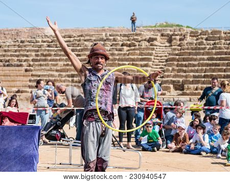 Caesarea, Israel, March 03, 2018 : A Participant Of The Purim Festival Juggles With Hoops For Visito