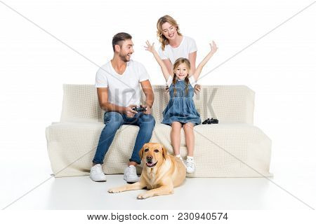 Excited Family Playing Video Game With Joysticks While Dog Sitting Near, Isolated On White