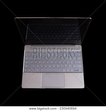 Opened Modern Gray Laptop With Us Keypad, Touchpad And Empty Mirror Screen On Black Background Top V