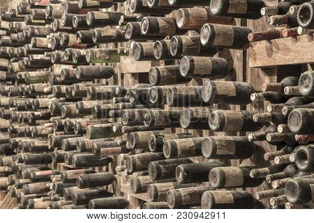 Many Old Wine Bottles Stacked On Wooden Racks