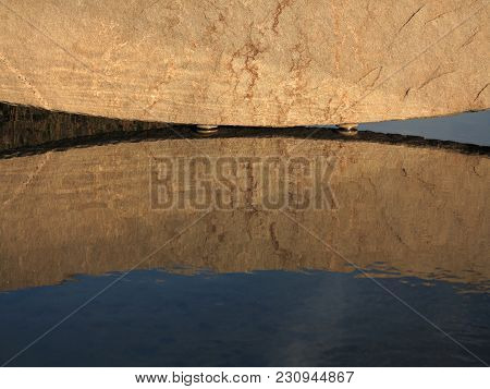 Big Brown Grunge Stone Reflection In Water As Background