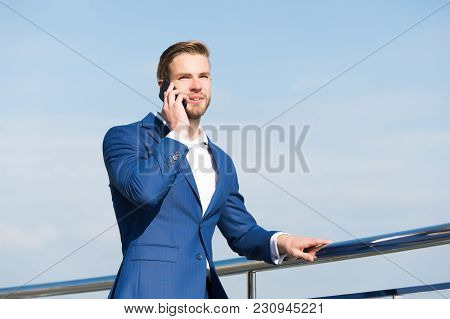 Man With Smartphone On Terrace On Blue Sky, Business Communication. Businessman In Business Suit Wit