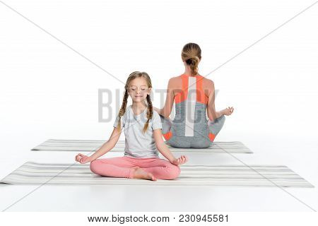 Athletic Mother And Daughter Practicing Yoga On Mats Together Isolated On White
