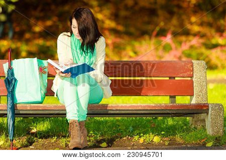 Woman Enjoying Beautiful Autumn Nature Weather, Reading Book Sitting On Bench In Park During Sunny A