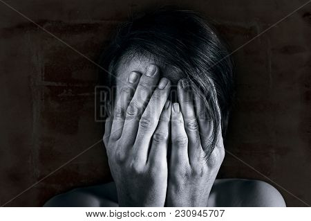 Concept Of Fear, Shame, Domestic Violence. Woman Covers Her Face By Hands On Dark Background. Black