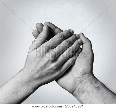 Male Hand Holds The Female Palm, Black And White Image. That Could Mean Help, Guardianship, Protecti