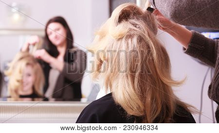 Beautiful Smiling Girl With Blond Wavy Hair By Hairdresser. Hairstylist Combing Female Client Young