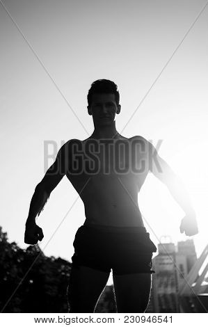 Sportsman Showing Muscular Body, Muscles, Biceps, Triceps On Blue Sky And Sunlight Background. Fitne