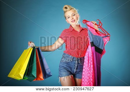 Retro Style. Shopper Woman Happy Shopping Buying Clothes. Pinup Girl Holding Olourful Shopping Bags