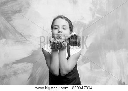 Baby Girl With Closed Eyes Enjoy Eating Cupcake On Colorful Abstract Wall. Small Little Cook In Red