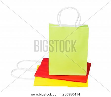 A Green Package Of Recycled Paper Stands On Folded Red And Yellow Packages.