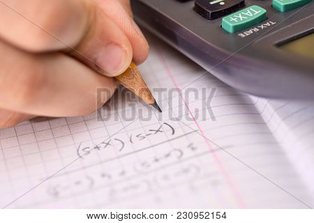 Child Holds The Pencil In His Hand And Solves Mathematical Problems. School, Education And Learning
