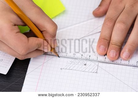 Mathematics Concept. Schoolboy Hands With Ruler Drawing On White Paper.