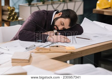 Overworked Young Architect Sleeping On Building Plans At Workplace