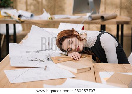 Overworked Female Architect Sleeping On Building Plans At Workplace