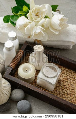 Spa setting with lying on gardenia , herbal, ball ,rolled towel ,oil ,salt in bottle,stones –gray background