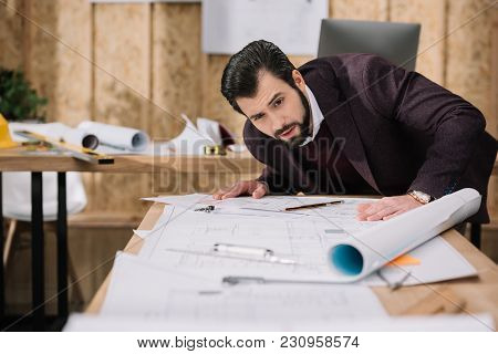View Of Surprised Young Architect Discovering Building Plans