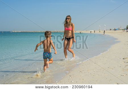 Happy Family Relaxing By The Sea. Happy Family Resting At Beach In Summer. Mother With Baby Boy Rest