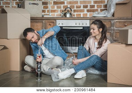 Happy Young Couple Opening Bottle Of Wine While Celebrating Relocation In New Apartment