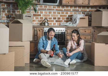 Young Couple With Bottle Of Wine Celebrating Relocation In New Apartment