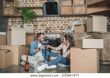 Happy Young Couple Drinking Wine And Celebrating Relocation In New Apartment