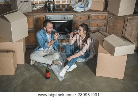 High Angle View Of Young Couple Drinking Wine And Celebrating Relocation In New Apartment