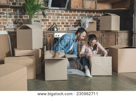 Smiling Young Couple Unpacking Boxes While Moving In New House