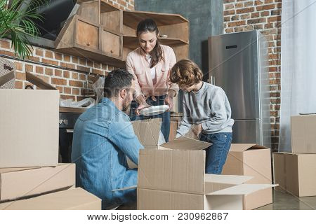Happy Family Unpacking Cardboard Boxes In New House