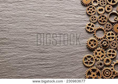 Various metal cogwheels and gear wheels over slate background