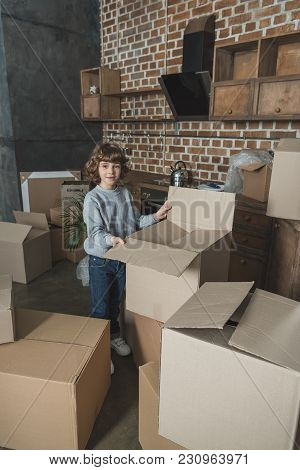 Cute Little Boy Smiling At Camera While Packing Boxes During Relocation
