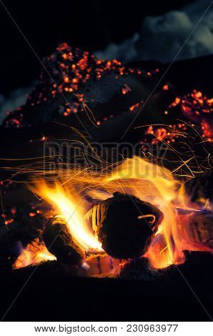 Burning Logs In Fire Pit With Cooking Dome