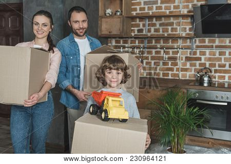 Happy Family Holding Cardboard Boxes And Smiling At Camera While Relocating
